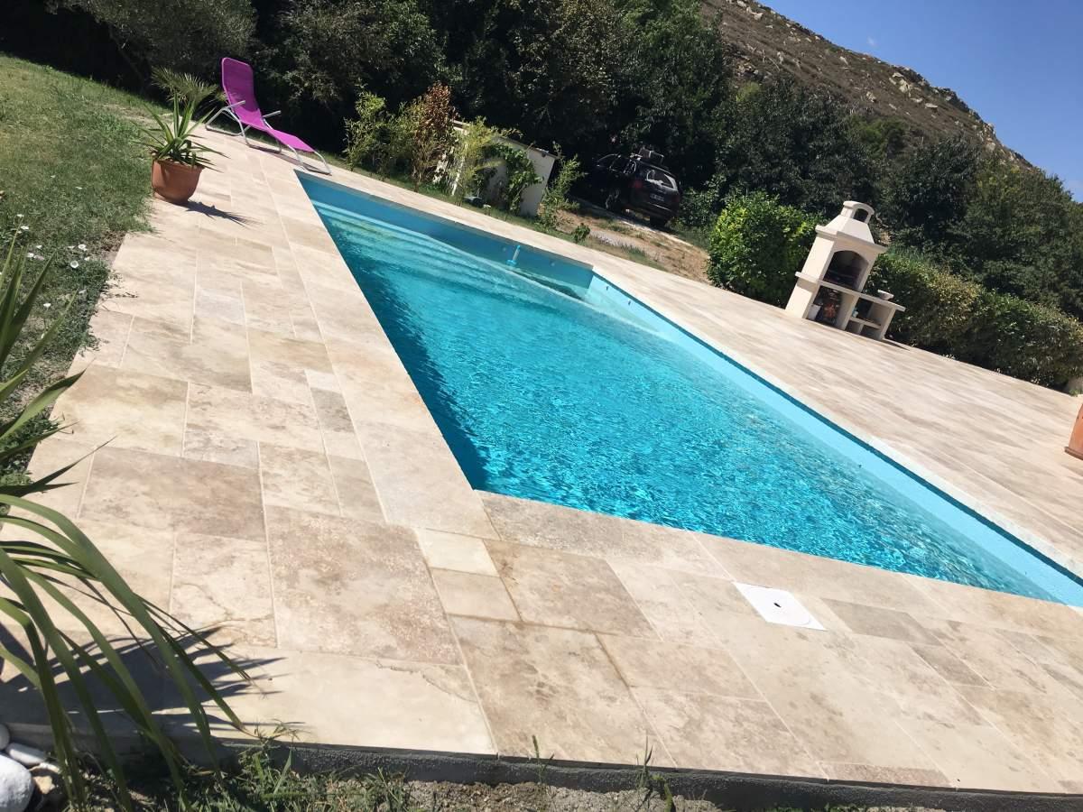 Terrasse en contour de piscine en opus de travertin bouche for Caniveau piscine miroir